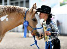 girl kissing prizewinning horse